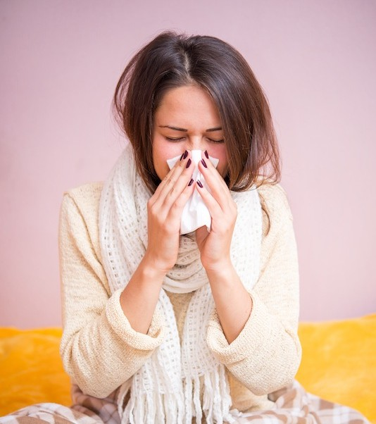 girl with a runny nose in bed, common cold or the flu
