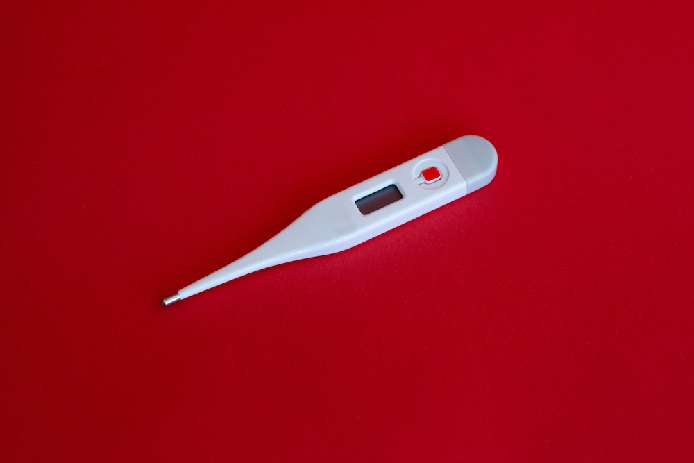 thermometer on red background - covid-19 flu season
