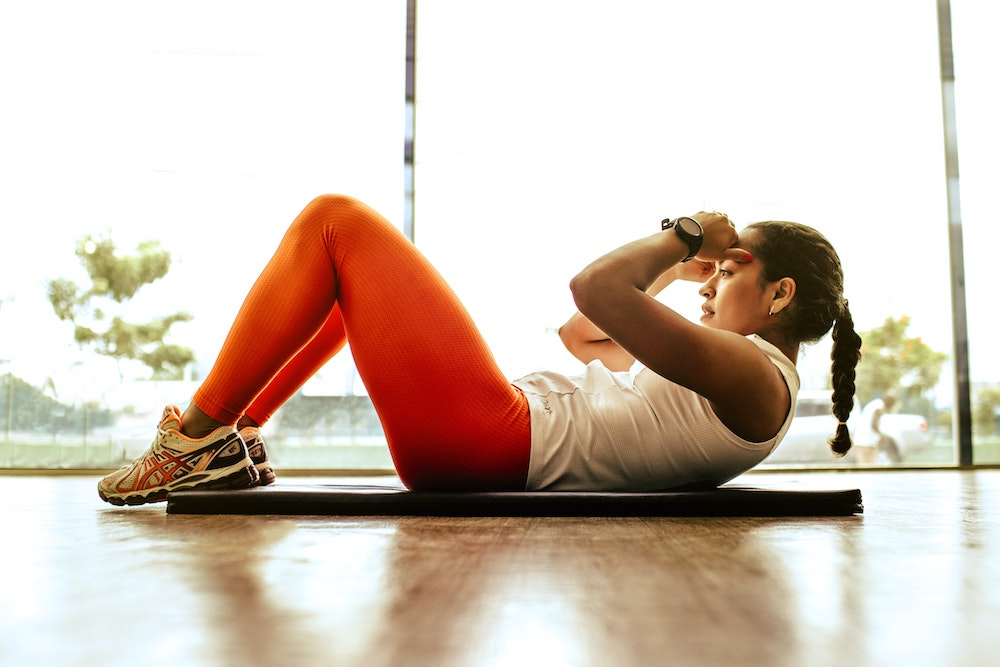 healthy resolutions - woman doing a sit up